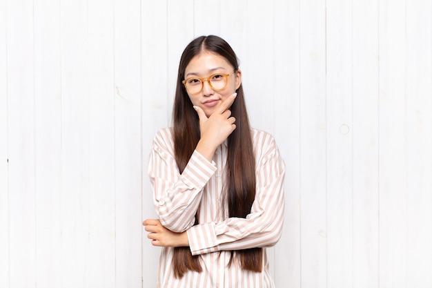 Aziatische jonge vrouw die ernstig, attent en wantrouwend kijkt