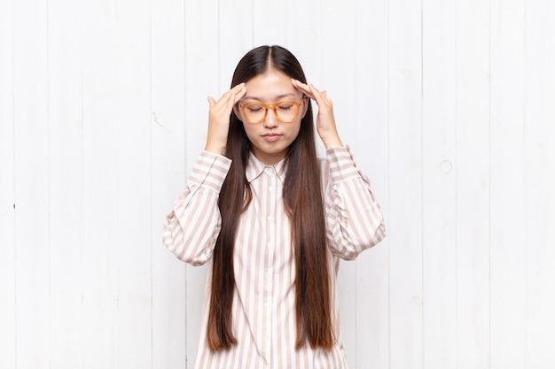 Aziatische jonge vrouw die geconcentreerd, attent en geïnspireerd geïsoleerd kijkt