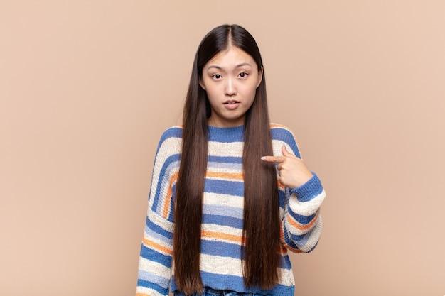 Aziatische jonge vrouw die geïsoleerd, verward, verbaasd en onzeker voelt