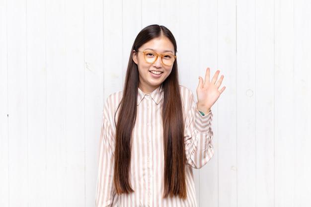 Aziatische jonge vrouw die gelukkig en vrolijk geïsoleerd glimlacht