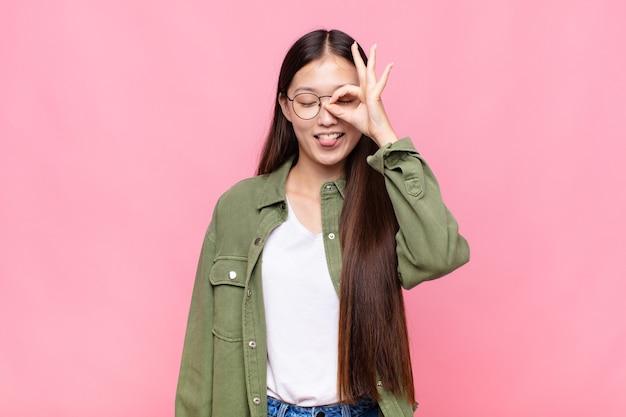 Aziatische jonge vrouw die gelukkig met grappig gezicht glimlacht, een grapje maakt en door kijkgaatje kijkt, geheimen bespioneert