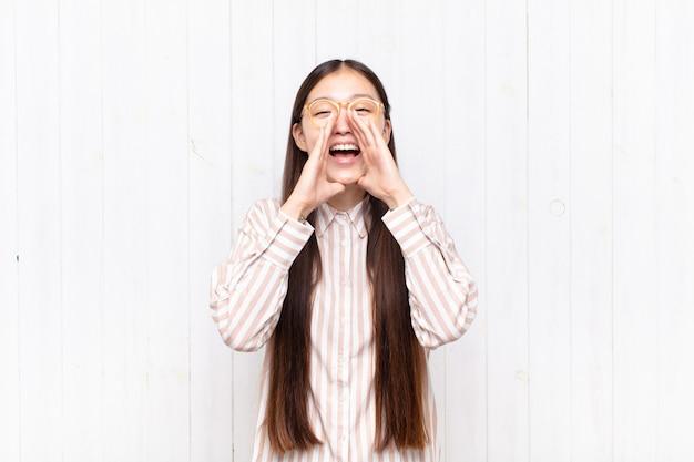 Aziatische jonge vrouw die gelukkig, opgewonden en positief geïsoleerd voelt