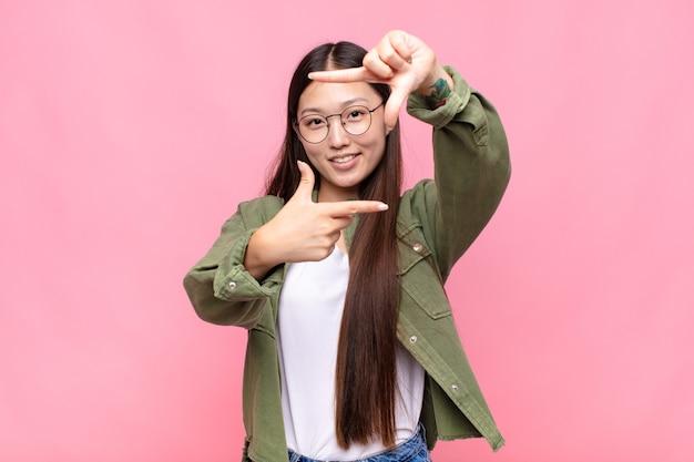 Aziatische jonge vrouw die gelukkig, vriendelijk en positief voelt, geïsoleerd glimlacht