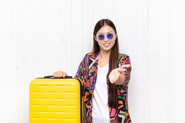 Aziatische jonge vrouw die, gelukkig, zelfverzekerd en vriendelijk glimlacht kijkt