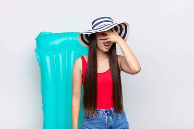 Aziatische jonge vrouw die geschokt, bang of doodsbang kijkt, gezicht bedekt met hand en tussen vingers gluurt