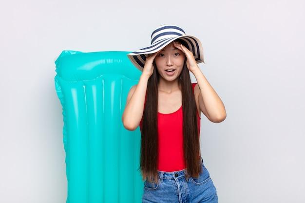 Aziatische jonge vrouw die geschokt en geschokt voelt, handen opheft tot het hoofd geïsoleerd