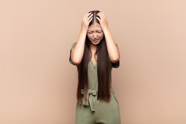Aziatische jonge vrouw die gestrest en gefrustreerd voelt, handen tegen het hoofd opheft