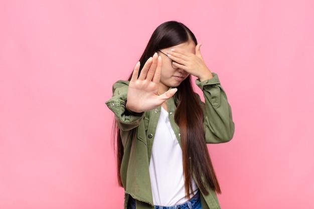 Aziatische jonge vrouw die gezicht bedekt met hand en andere hand op de voorgrond zet om de camera te stoppen, foto's of afbeeldingen weigeren