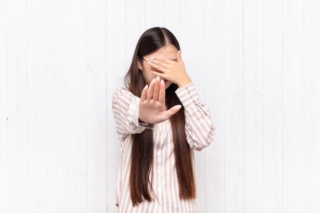 Aziatische jonge vrouw die gezicht bedekt met hand en andere hand voorop zet om te stoppen, foto's of afbeeldingen weigeren