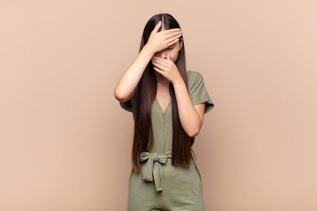 Aziatische jonge vrouw die gezicht behandelt met beide handen die geïsoleerd nee zeggen