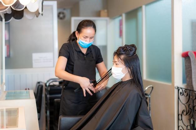 Aziatische jonge vrouw die gezichtsmaskers draagt om zichzelf tegen covid-19 te beschermen tijdens kapper die zwart haar met schaar in schoonheidssalon in orde maakt.