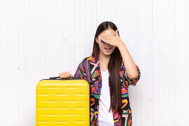 Aziatische jonge vrouw die glimlacht en zich gelukkig voelt, ogen met beide handen bedekt en op ongelooflijke verrassing wacht.