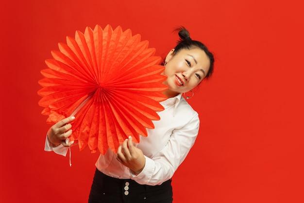 Aziatische jonge vrouw die grote lantaarn op rode muur houdt