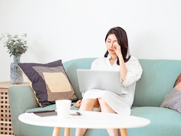 Aziatische jonge vrouw die haar vermoeide ogen wrijft bij het gebruik van een laptop.