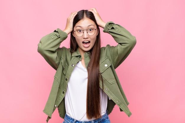 Aziatische jonge vrouw die handen opheft aan het hoofd, met open mond geïsoleerd