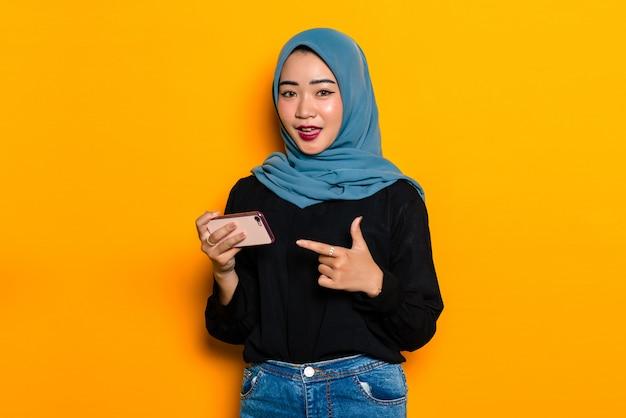 Aziatische jonge vrouw die hijab draagt en smartphone houdt