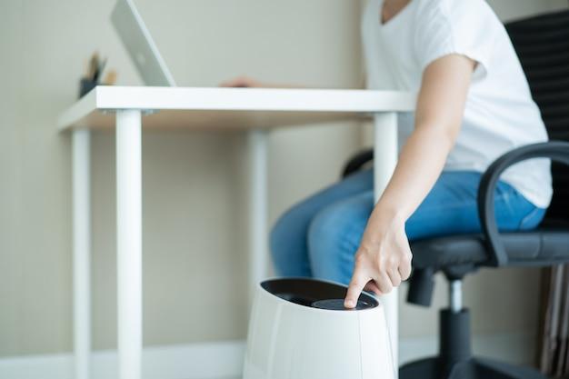 Aziatische jonge vrouw die in het kantoor aan huis werkt en een luchtreiniger gebruikt, een meisje dat op de bank zit en een laptop gebruikt.