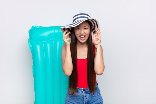 Aziatische jonge vrouw die in paniek of woede gilt, geschokt, doodsbang of woedend, met de handen naast het hoofd. zomer concept
