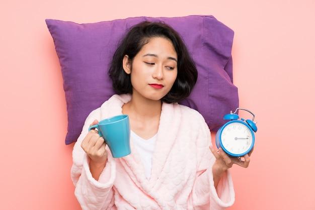 Aziatische jonge vrouw die in pyjama een kop van koffie en een klok houdt