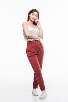Aziatische jonge vrouw die in volledige lengte op witte muur loopt.