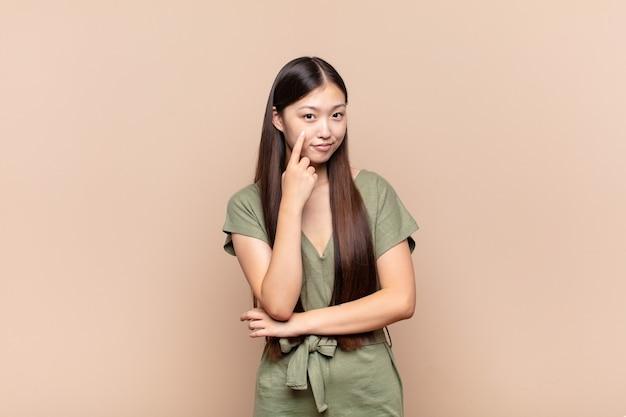 Aziatische jonge vrouw die je in de gaten houdt, niet vertrouwt, kijkt en alert en waakzaam blijft