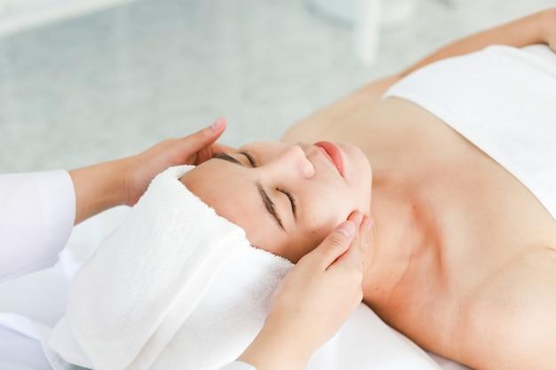 Aziatische jonge vrouw die kuuroordbehandeling krijgt bij schoonheidssalon. spa gezichtsmassage. gezicht schoonheidsbehandeling