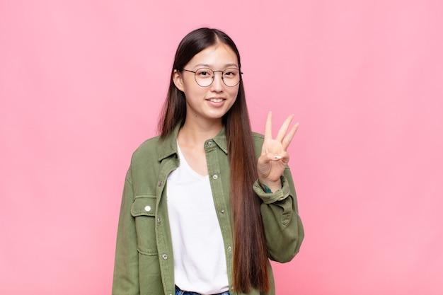 Aziatische jonge vrouw die lacht en er vriendelijk uitziet, nummer drie of derde toont met de hand naar voren, aftellend