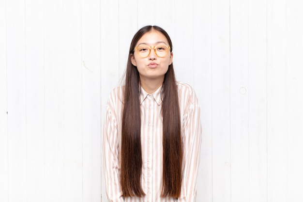 Aziatische jonge vrouw die lippen samen met een leuke, leuke, gelukkige, mooie uitdrukking drukt, een kus verzendt