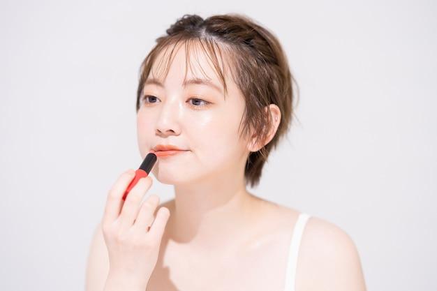 Aziatische jonge vrouw die lippenstift en witte achtergrond toepast