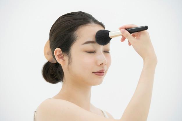 Aziatische jonge vrouw die make-up met een zachte borstel toepast