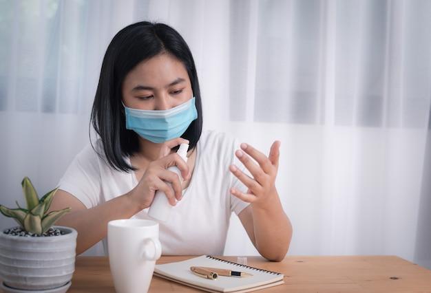 Aziatische jonge vrouw die masker en spuitalcoholfles draagt om tegen coronavirusepidemie te beschermen