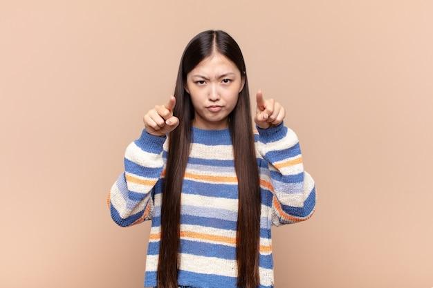 Aziatische jonge vrouw die met beide vingers en een boze uitdrukking naar voren wijst en je vertelt je plicht te doen