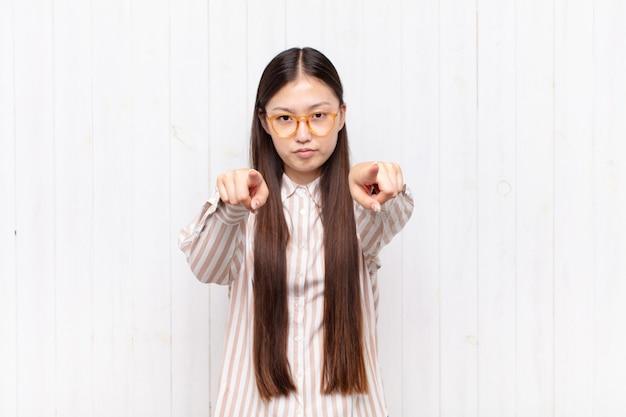 Aziatische jonge vrouw die met beide vingers vooruit op camera richt