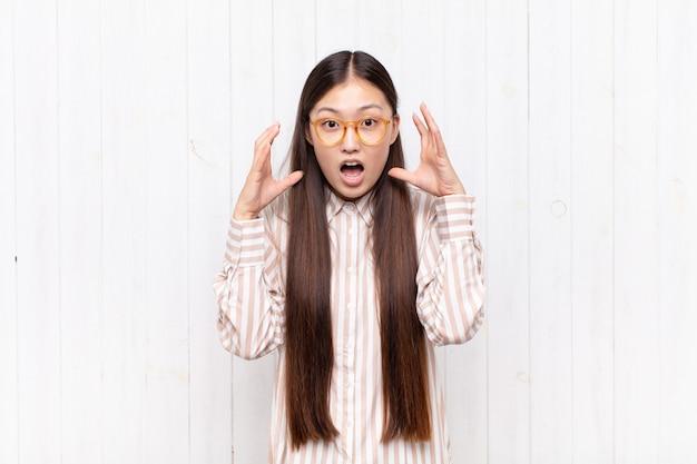 Aziatische jonge vrouw die met handen in de lucht schreeuwt, woedend, gefrustreerd, gestrest en boos voelt