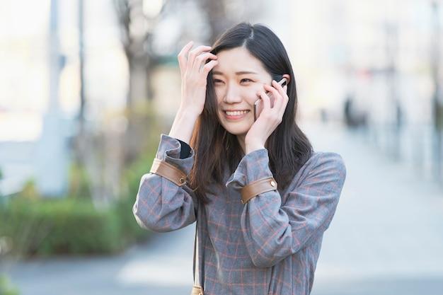 Aziatische jonge vrouw die met iemand met smartphone op oor spreekt