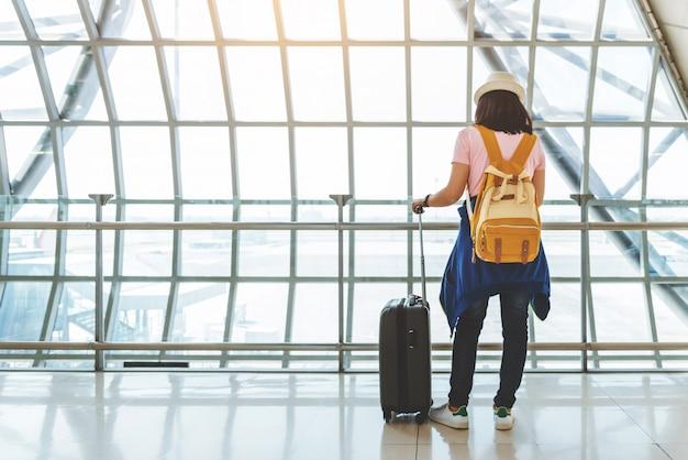 Aziatische jonge vrouw die met koffer en gele rugzak op de vlucht bij venster van de luchthaven wacht.