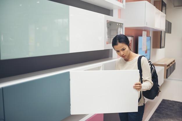 Aziatische jonge vrouw die meubilair in een moderne opslag van het huismeubilair kiezen