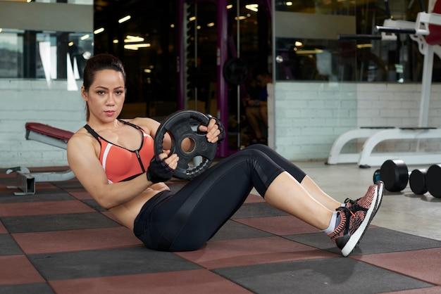 Aziatische jonge vrouw die oefening met gewichtsplaat doet in een gymnastiek