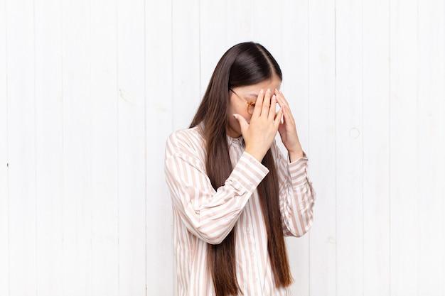 Aziatische jonge vrouw die ogen bedekt met handen met een droevige, gefrustreerde blik van wanhoop, huilend, zijaanzicht