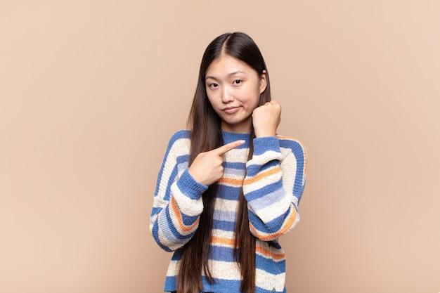 Aziatische jonge vrouw die ongeduldig en boos kijkt, wijzend op horloge