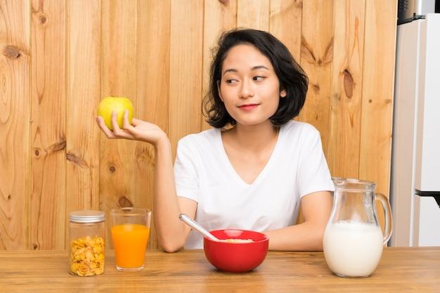 Aziatische jonge vrouw die ontbijt en met een appel heeft
