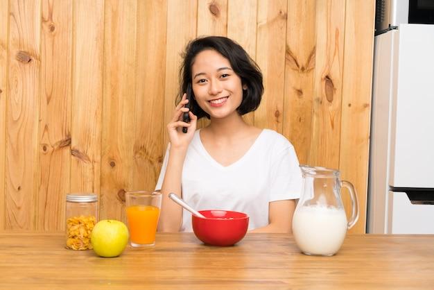 Aziatische jonge vrouw die ontbijt heeft dat een gesprek met mobiel houdt