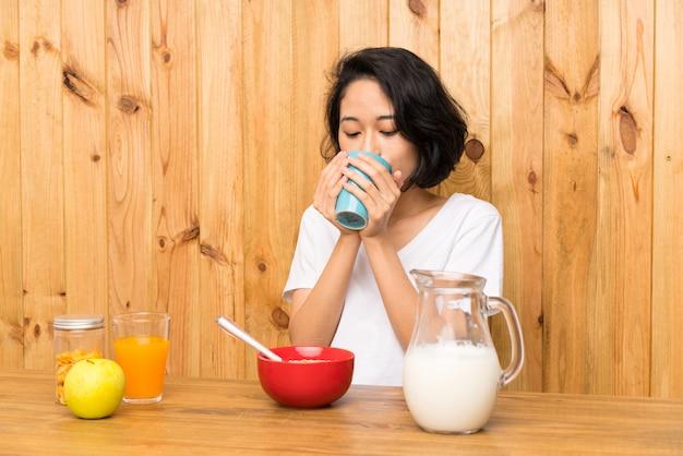 Aziatische jonge vrouw die ontbijt heeft dat een kop van koffie houdt