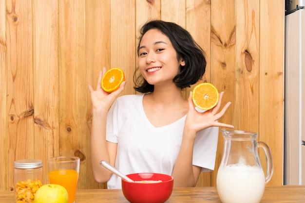 Aziatische jonge vrouw die ontbijt heeft dat een sinaasappel houdt