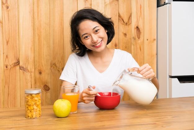 Aziatische jonge vrouw die ontbijt heeft