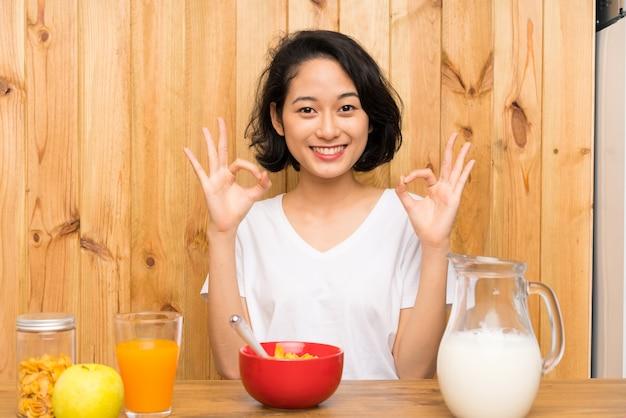 Aziatische jonge vrouw die ontbijtmelk heeft die een ok teken met vingers toont