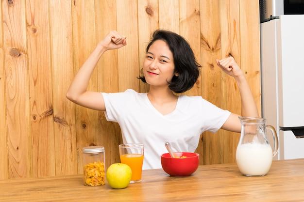 Aziatische jonge vrouw die ontbijtmelk heeft die een overwinning viert
