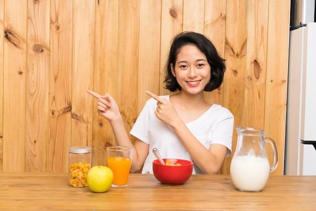 Aziatische jonge vrouw die ontbijtmelk heeft die vinger richt aan de kant