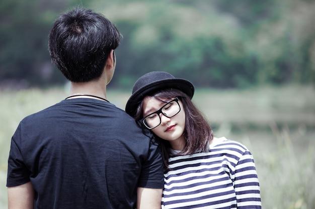 Aziatische jonge vrouw die op de schouder van haar vriend met liefde binnen rusten