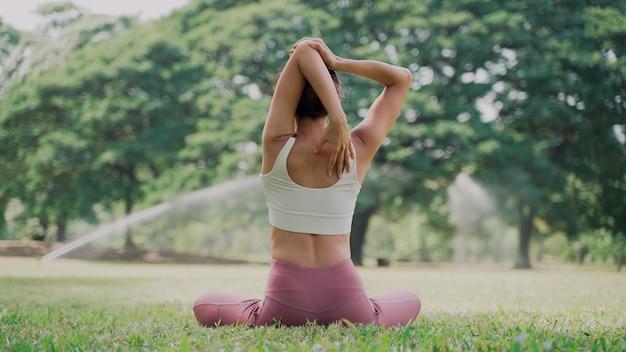 Aziatische jonge vrouw die op het gras zit en yoga beoefent in de positie van de koe in het stadspark met de achtergrond van de grote bomen. achteraanzicht van een vrouw die op een zonnige dag buiten yoga beoefent.